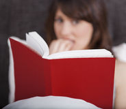 Reading a terror story. Young woman reading a terror storie with a terrified expression stock photography