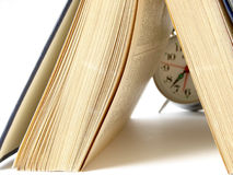 Reading time. Open book and classic alarm clock Royalty Free Stock Photos