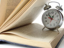 Reading time 4. Open book and classic alarm clock Stock Photo
