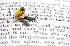 Reading Time. Miniature person reading while sitting on page of book Royalty Free Stock Image