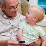 Reading to child. Grandfather reading book to grand child, smiling stock images