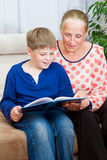 Reading to me. Grandmother and grandson are reading Stock Images