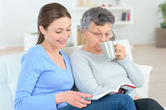 Reading to old lady Stock Image