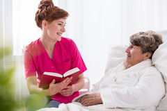 Reading to old woman Stock Images