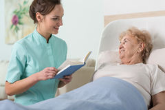 Reading to older woman. Young beautiful nurse reading to sick older women in bed Stock Photography