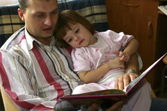 Reading together. Child and father reading together Stock Image