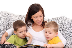 Reading together. Mother and two sons reading book in bed Stock Photography