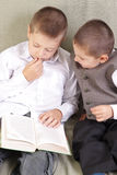 Reading together. Two boys reading book together Royalty Free Stock Photos