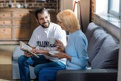 Polite clever volunteer reading a book with a nice senior woman. Reading together. Cheerful kind volunteer looking happily at the aged women while sitting on the Royalty Free Stock Photography