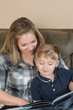 Reading Together. A mother and her young son snuggle together as she reads a story to him stock photo