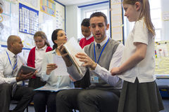 Reading Together. Some students each sit with a teacher practising and learning to read at the front of the class stock photography