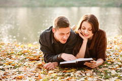 Reading together. Young male and female lying down near lake reading book Royalty Free Stock Photos