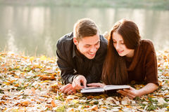 Reading together. Young male and female lying down near lake reading book Stock Photo