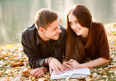 Reading together. Young male and female lying down near lake talking smiling Stock Image