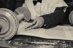 Reading a Torah scroll during a bar mitzvah ceremony . Reading a Torah scroll during a bar mitzvah ceremony with a traditional yad pointing towards the text on Stock Images