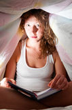 Reading under cover Stock Photography