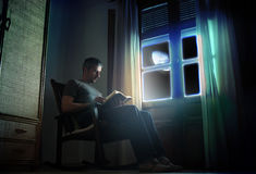 Reading under the moonlight. A man in a rocking chair, reading near a window under the moonlight royalty free stock photo