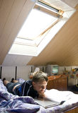 Reading under skylight Stock Photo