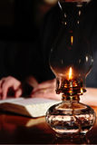 Reading By Vintage Lamplight. A person reads a Bible or book by the light of an antique oli lamp (shallow focus point on oil lamp stock photos