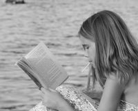 Reading water. Ryley reading by the water stock image