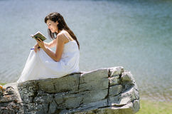 Reading and water. Woman reading a book in nature with water background Royalty Free Stock Photography