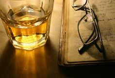 Reading with Whiskey. Whiskey Tumbler Glasses and old book Stock Images