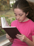 Reading By Window Light. A girl reading from a book (hymnal) by window light Royalty Free Stock Photos