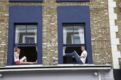 Reading in the window. Two people reading newspapers in Notting Hill Stock Images