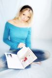 Reading woman. A young, blond woman is reading a magazine Stock Photo