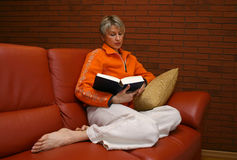 Reading woman #3. Reading woman on a red sofa Stock Photos