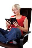 Reading woman in armchair Royalty Free Stock Photos