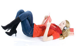 Reading woman in headphones lying on heap of books Royalty Free Stock Photo