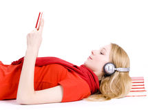 Reading woman in headphones lying on heap of books Stock Images