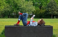 Reading woman in the park. Mature curly haired woman reads or lerans in the park Stock Photos