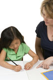 Reading and Writing. A young girl learns to write with the help of a teacher Stock Photo