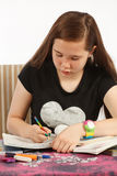 Reading and Writing Homework. Young girl reading and writing her homework Royalty Free Stock Photo