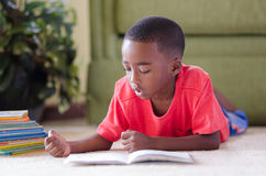 Reading. A young African American boy laying on the floor reading a book Stock Photo