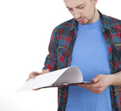 Reading young man with clipboard Royalty Free Stock Images