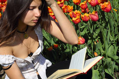 Reading young woman. On spring tulips background Royalty Free Stock Images
