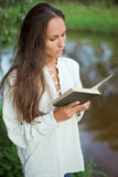 Reading young woman near the river. Reading young woman with book near the river Royalty Free Stock Photography
