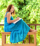 Young woman writing to notebook Royalty Free Stock Image