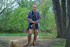 Native American with  dugout canoe with rifle Royalty Free Stock Photo