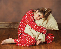 Ready for Bed. A young preteen in polka-dot pajamas hugging her pillow Stock Image