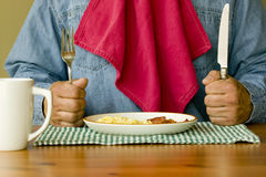 Ready For Breakfast. Hungry man holding knife and fork with napkin tucked in shirt ready to eat bacon and eggs for breakfast Stock Photo