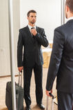 Ready for business trip. Confident young man in formalwear adjusting his necktie while standing against mirror in hotel room Royalty Free Stock Photography