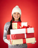 Ready for Christmas. Portrait of lovely girl in winterwear holding wrapped gifts stock photo