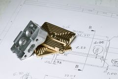 Ready CNC golden and silver metal detail on technical drawing sketch Royalty Free Stock Image