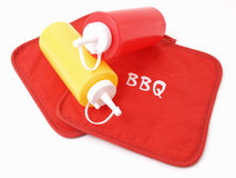 Ready for the Cookout. Ketchup and Mustard squeeze bottles laying on two red potholders Royalty Free Stock Photography