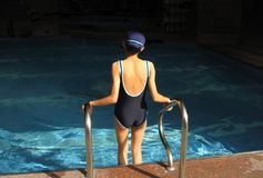 Ready for a Dip. Young girl getting into a swimming pool Royalty Free Stock Photos