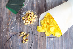 Ready for drinking beer: potato chips in paper cone, pistachios, coasters. Royalty Free Stock Photos